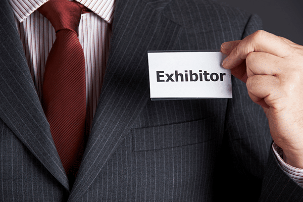 A close up of a name tag on a person in a suit, the name tag reads Exhibitor.