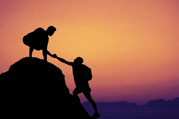 Two people climbing up a mountain in the sunset and one person is helping the other peson up by reaching out and holding their hand.