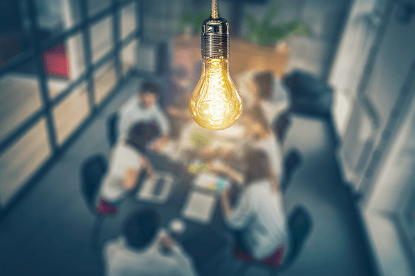 A close up in a lightbulb hanging in the ceiling above a conference room table where there is a meeting going on.