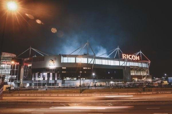 Photo of The Ricoh Arean at night lit up by street lights.