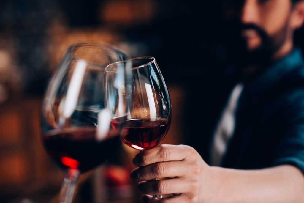 A close up of two wine glasses being raised and clinking together.