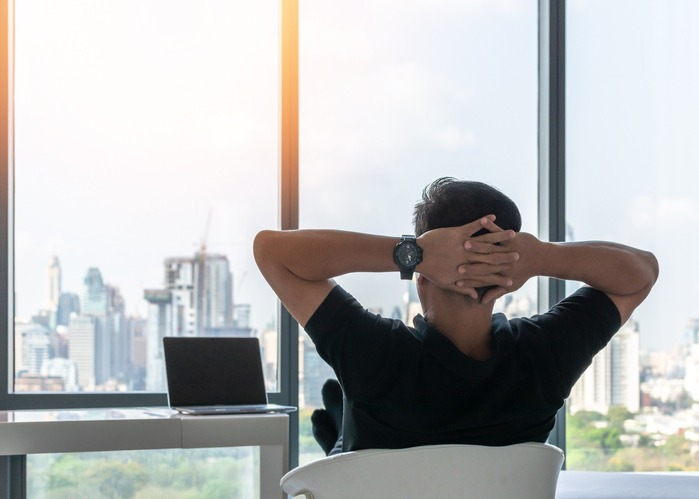 Life-work balance and city living life style concept of business man relaxing, take it easy in office room resting with thoughtful mind thinking of lifestyle quality looking forward to cityscape