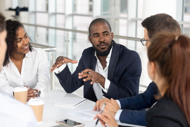Black millennial boss leading corporate team during briefing in boardroom
