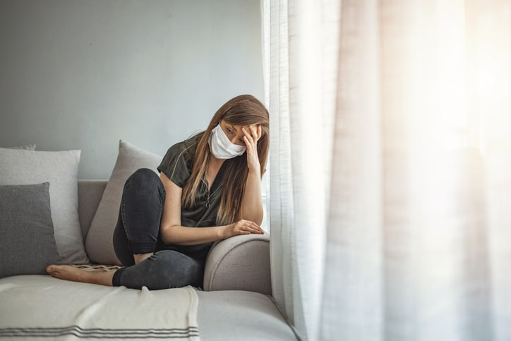 Sad lonely girl isolated stay at home in protective sterile medical mask on face looking at window