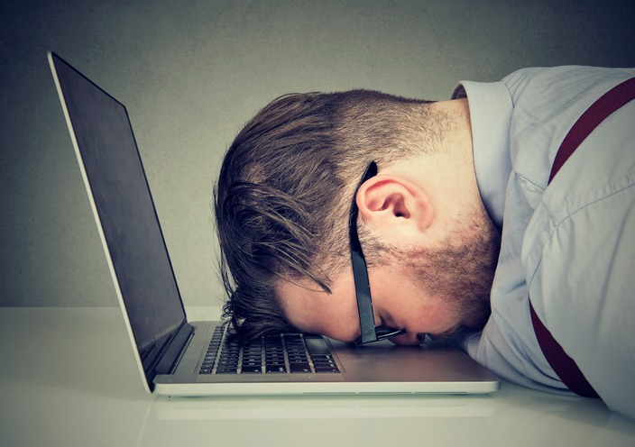 Overworked man lying on laptop