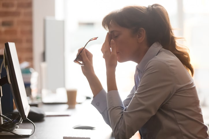 Tired female employee suffer from headache at workplace