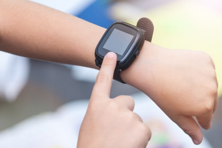 A close-up of child`s hands with smart watch. Touching electronic watch.