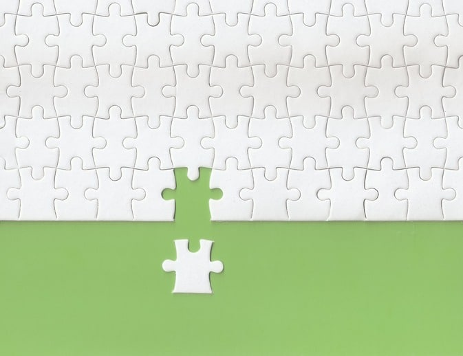 Green background made from white puzzle pieces and copy space for content
