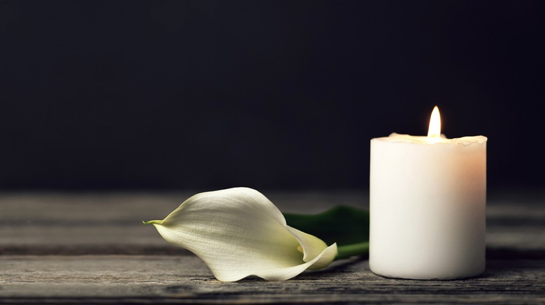 Burning candle and white calla on dark background with copy space. Sympathy card