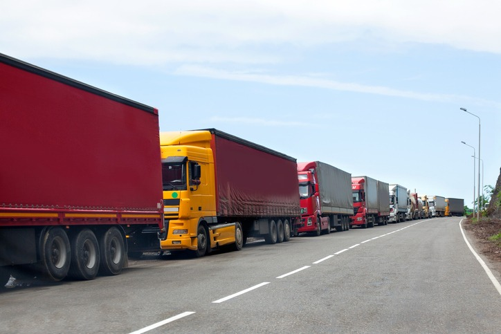 Queue of trucks passing the international border, red and different colors trucks in traffic jam on the road
