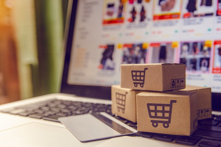 Shopping online concept – Shopping service on The online web. with payment by credit card and offers home delivery. parcel or Paper cartons with a shopping cart logo on a laptop keyboard